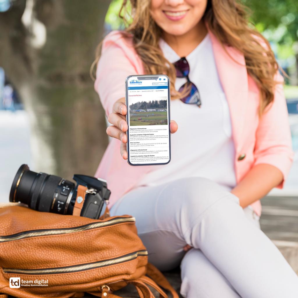 Die neue Webseite der Stadt Schlüchtern, erstellt von team digital, auf einem Smartphone einer jungen Frau